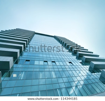 square side of pane in business center over blue bright sky - stock photo