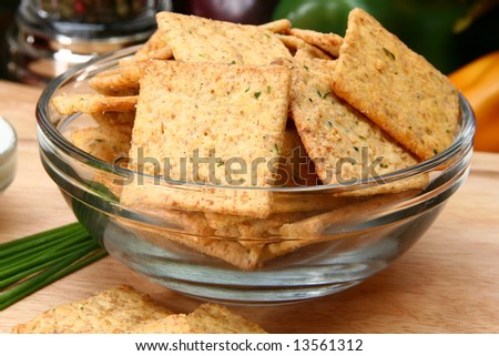 Square sour cream and chive flavored crackers in glass bowl on cutting board in kitchen or resturant.