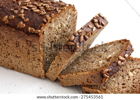 Square sunflower seed loaf sliced on rustic white surface. - stock photo