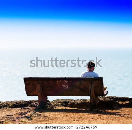 Square vivid young man reading book on bench on ocean beach background backdrop