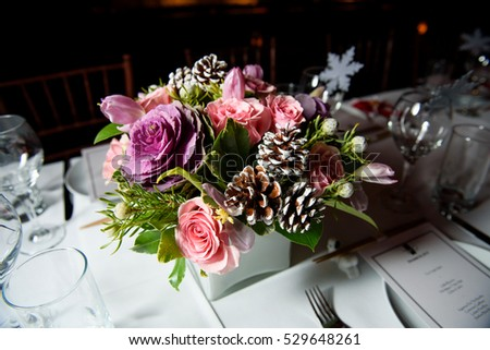 Square white flowerpot with pink and violet roses stands on elegant served dinner table