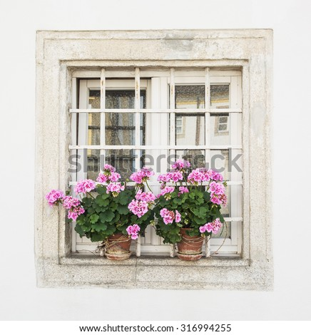 Square window decorated with potted flowers. Building facade. - stock photo