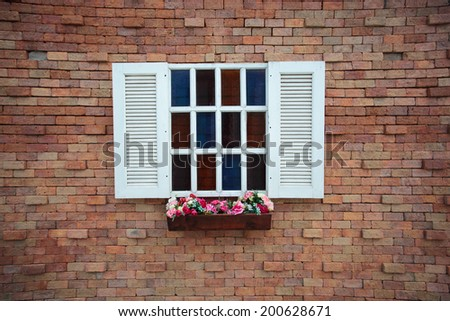 Square window on the brick wall and flower - stock photo