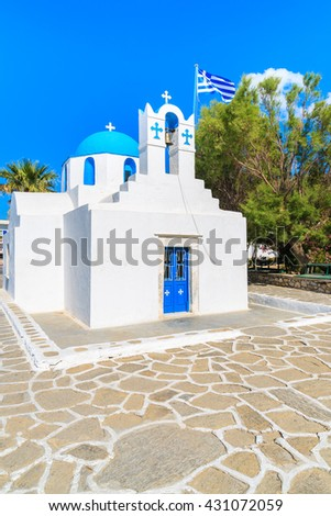 Square with typical white church with blue dome and Greek flag on Paros island, Cyclades, Greece - stock photo