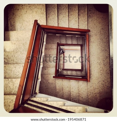 Squared downstairs with wood railing. - stock photo