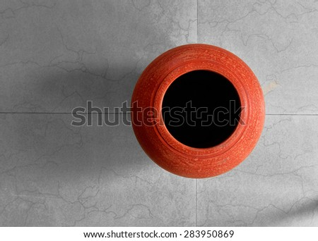 Squares and circles. A red clay pot on tiled floor. view from top. Terracotta for interior decoration. Geometric lines and patterns. - stock photo