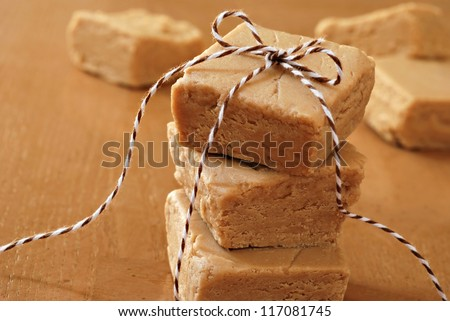 Squares of creamy peanut butter fudge stacked and tied with festive bakers twine for holiday gift giving.  Macro with extremely shallow dof. - stock photo