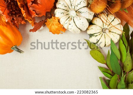 Squash and imitation leaves, berries and wild flowers form a border and background on woven fabric background with copy space for fall & Thanksgiving themes.  - stock photo