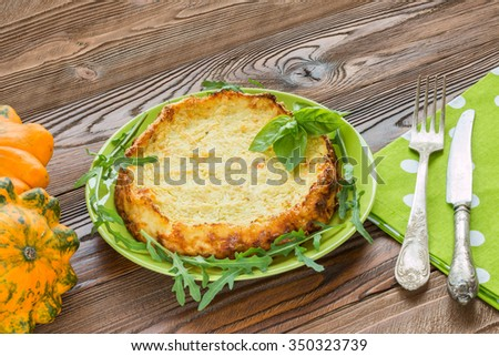 squash casserole decorated by basil leaf and arugula on light green plate at wooden table with squash fruits and light green napkins at white polka dots pattern and old silver cutlery