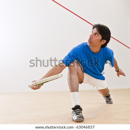 Squash player hiting a backhand lob shot in a squash court. - stock photo