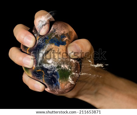 Squashed Earth in a clenched fist. A conceptual image for the human impact on the planet. Elements of this image furnished by NASA. - stock photo