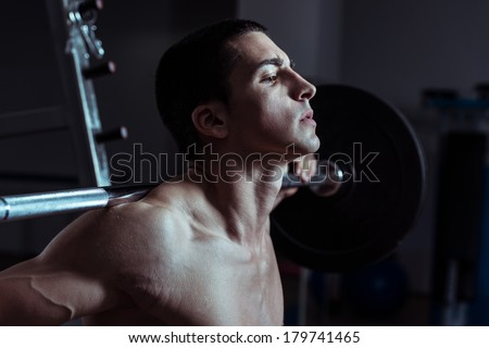Squats - Young Man Performing Barbell Squats - One Of The Best Body Building Exercise For Legs - stock photo