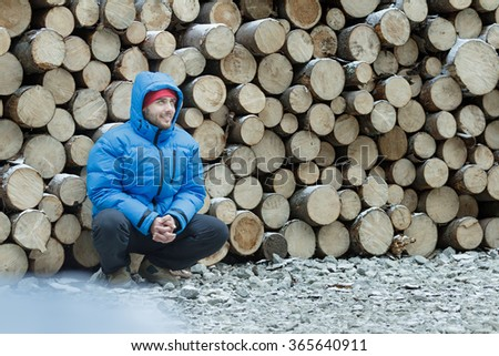 Squatting lumberjack at stack of logged firewood background outdoors in winter mountain forest - stock photo