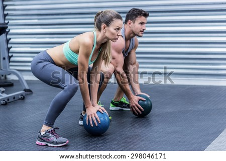 Squatting muscular couple doing ball exercise - stock photo