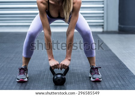 Squatting muscular woman lifting kettlebells at the crossfit gym - stock photo