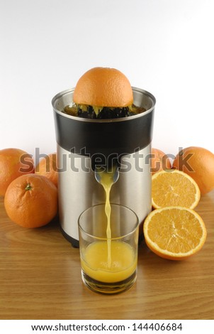 squeezer pouring orange juice into a glass
