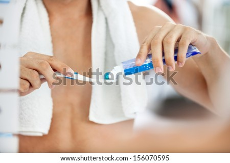 squeezes toothpaste on the brush - stock photo
