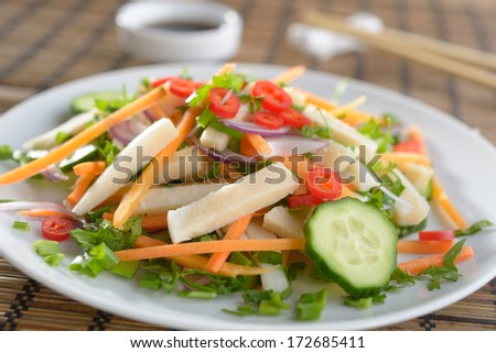 Squid salad with carrot, onion, cucumbers, chili peppers, and soy sauce - stock photo