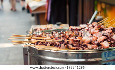 Squid skewers on a grill at the streetmarket in Insadong, Seoul. - stock photo