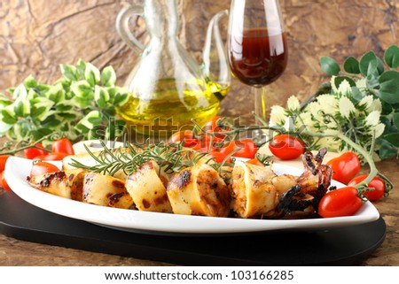 Squid stuffed with bread crumbs and tomatoes on complex background - stock photo