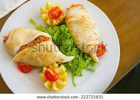 Squid stuffed with seafood in white plate, top view - stock photo