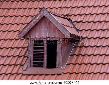 squint window on red roof - stock photo