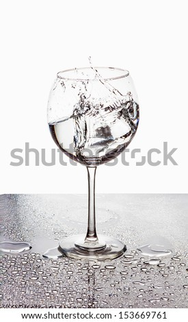 Squirt in glass in drops of water - stock photo