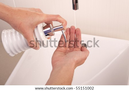 Squirting liquid soap into the palm of a hand - stock photo