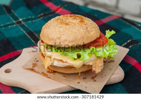 Sreet food  - burger with grilled chicken fillet, cheese and vegetables on wooden board close up selective focus - stock photo