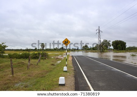 sri lanka landscape with flood waters rising to cover the highway near pottuvil