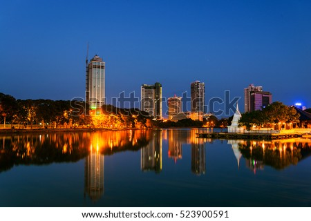 Sri Lanka. View of Beira Lake in Colombo, Sri Lanka with buddhist temple and illuminated modern buildings at night. Dark blue sky