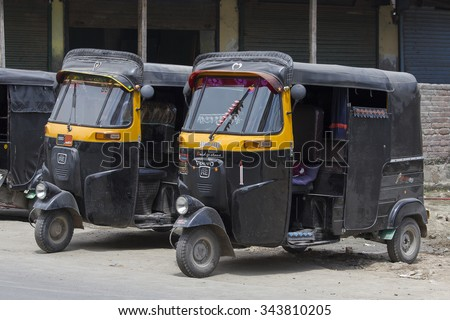SRINAGAR, INDIA - JULE 02, 2015: Auto rickshaw taxis on a road in Kashmir, India. These iconic taxis have recently been fitted with CNG powered engines in an effort to reduce pollution