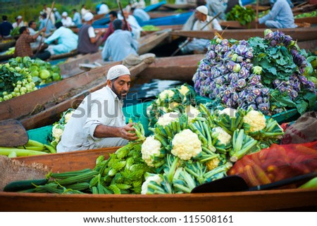SRINAGAR, INDIA - JULY 17: A Kashmiri man transfers vegetables from his shikara boat at the floating market on Dal Lake, a tourist attraction, in Kashmir on July 17, 2009 in Srinagar, India - stock photo