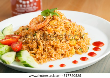 Sriracha shrimp fried rice dish with garnish dots of siracha sauce. - stock photo
