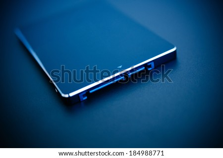 SSD disk drive in blue technological background - tilt-shift lens used to accent the center of the hdd and to emphasize the attention its connections - stock photo