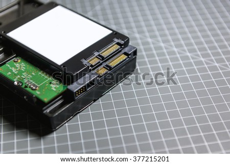 Ssd disk (solid state drive) above the HDD (hard disk drive) disk on hacker table - stock photo