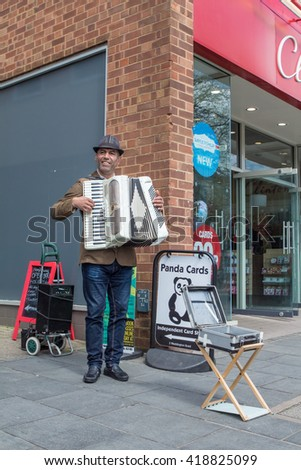 ST ALBANS, UK - MAY 3, 2016: A busker plays his accordion on St Peters Street - stock photo