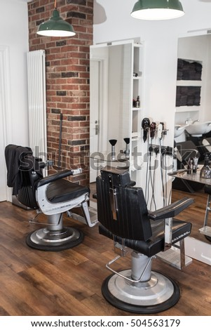 ST ALBANS, UK - OCTOBER 20, 2016: Interior of male hair salon with empty pedestal chairs