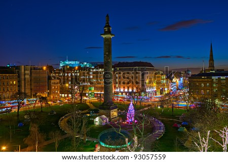 St Andrew's Square, Edinburgh, Scotland, UK, Europe, at dusk, at Christmas time.  The Melville monument is in the centre of the square.  The illuminated Castle is visible in the background. - stock photo