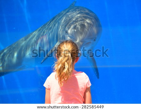 ST. AUGUSTINE, FLORIDA - APRIL 22: Child at Marineland  interacting with dolphin. Tourist enjoy their visit seeing dolphins playing . Event was on April, 22, 2015 at St. Augustine, Florida. - stock photo