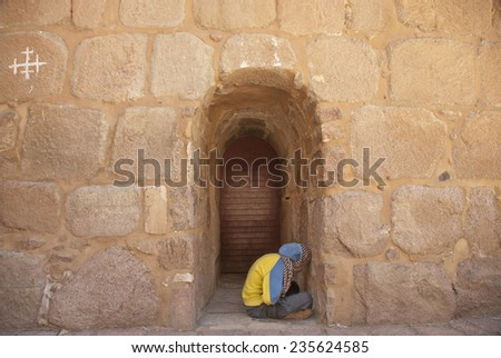 ST. CATHERINE'S MONASTERY, EGYPT - MAY 19: Unidentified pilgrim waits start a church service at the gate of Monastery, Egypt, May 19, 2011. St. Catherine's  Monastery is sacred for all Christians. - stock photo