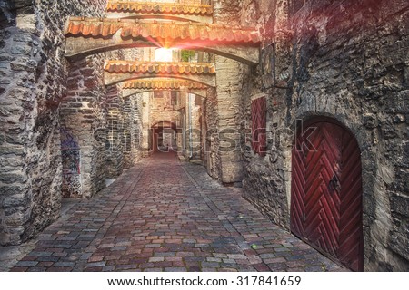 St. Catherine's Passage in Tallinn, Estonia. A sunlight through the window shining at the little walkway in the old city. Lens flares - stock photo