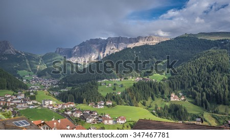 St. Christina, a summer and winter holiday village in Val Gardena, after a thunderstorm. Selva village, Sella group (on the right) and Stevia lighted summit are seen in the background, Dolomites