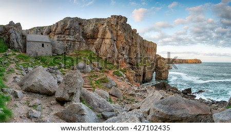 St Govan's Chapel, a tiny hermit cell built in to limestone cliffs on the rugged south Pembrokeshire coast in Wales - stock photo