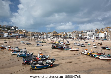 St Ives Harbor at low tide with several mainly fishing boats waiting for high tide - stock photo