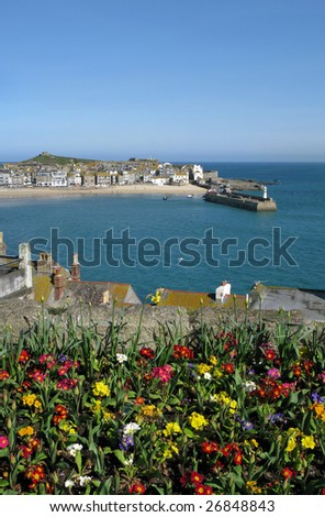 St. Ives harbour with colourful spring flowers in the foreground. - stock photo