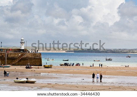 st ives, the summer resort harbor of cornwall, with lighthouse in distance as background - stock photo