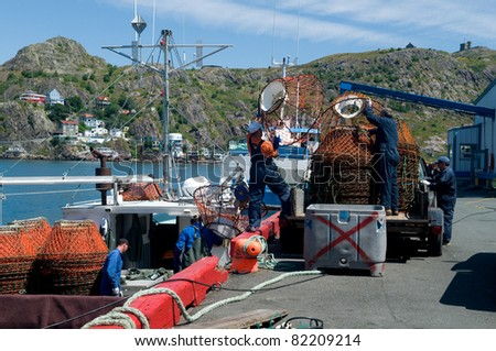 ST. JOHN'S, NEWFOUNDLAND - AUGUST 1: Fishermen stack dozens of crab pots on the harbor docks marking the end of the snow crab season in St. John's, Newfoundland on Aug. 1, 2009. - stock photo
