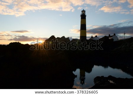 St. John's Point Lighthouse, located in Co. Down, displays a beautiful sunset. Famous for being yellow and black in color, the lighthouse is reflected beautifully in the pool of water.