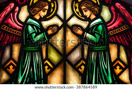ST. JOSEPH, MN - MARCH 7, 2016: Stained glass window of two angels kneeling in prayer - stock photo